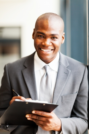 smiling african american office worker writing report in office photo
