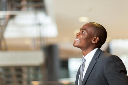 american african: ottimista uomo d'affari americano africano che osserva in su Archivio Fotografico