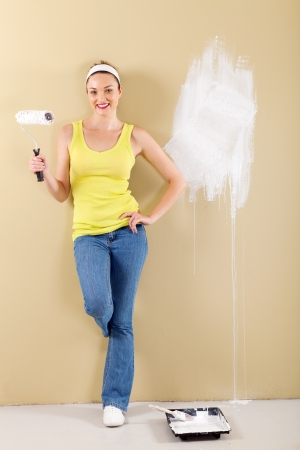 full length of young woman painting the wall photo