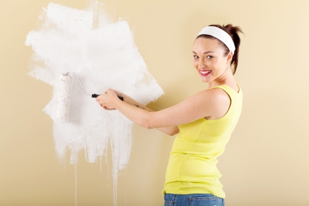 beautiful young woman painting new home with roller photo