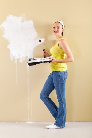 happy young woman painting the wall at home photo