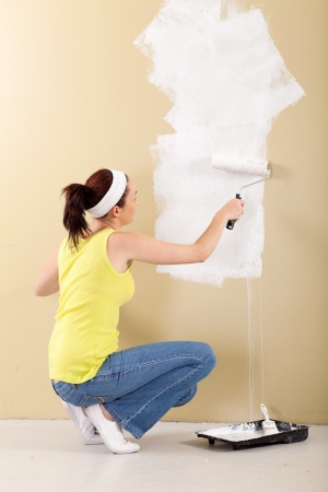 young woman painting the wall in her new home photo