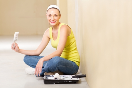 attractive young woman taking a break while painting her new home photo