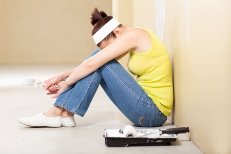 young woman feeling tired after painting the house photo