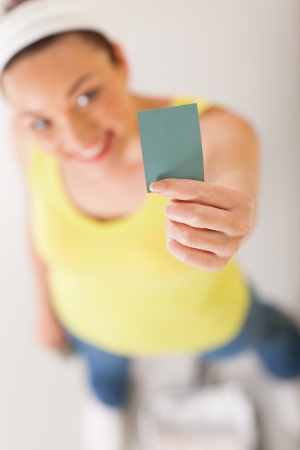 color chart: happy young woman holding and presenting paint color chart