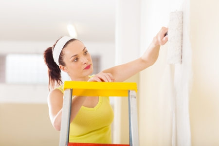 beautiful young woman painting new home photo
