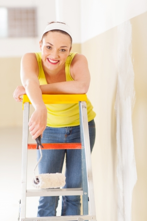 happy young woman standing on ladder with painting roller photo