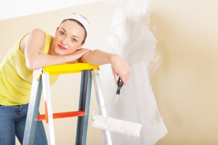 young woman standing on ladder and resting while paint new home photo