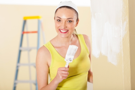 happy young woman painting new house photo