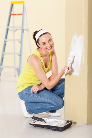 happy young woman painting new home photo