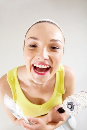 laughing young woman with paintbrush and roller photo