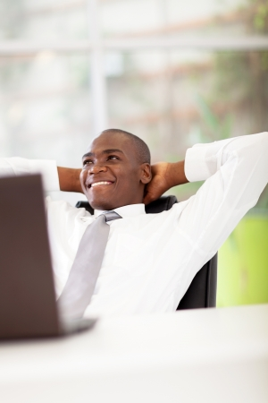 african american businessman daydreaming in office photo