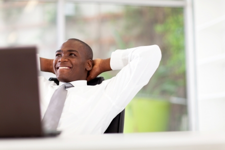 african businessman: happy african american businessman relaxing in office Stock Photo