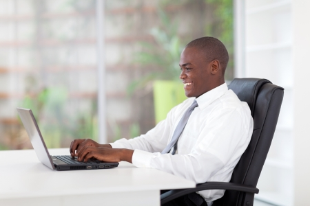 african business: young african businessman working on laptop in office Stock Photo