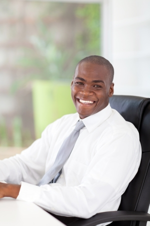 happy young african businessman sitting in front of desk in office Stock Photo - 16825064