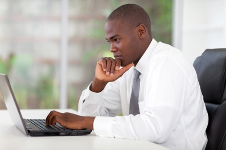 sitting at desk: thoughtful young african american businessman working on laptop computer
