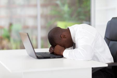 personas tristes: deprimido empresario afroamericano a la cabeza en la computadora port�til