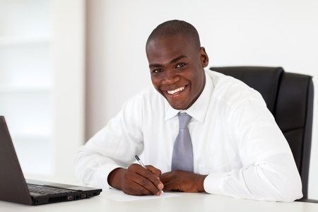 happy african american businessman writing report photo