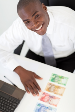 happy young african businessman with bank notes on his desk photo