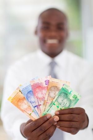 rand: young south african businessman holding new bank notes