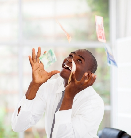 rand: african businessman catching money falling from above Stock Photo