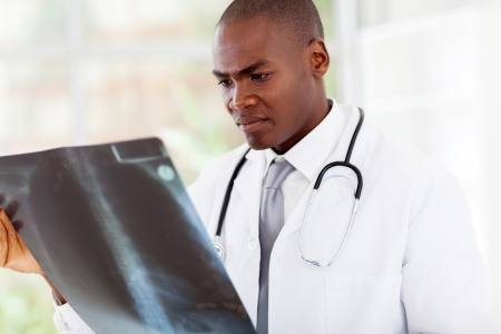 ct scan: african american doctor looking at patients x-ray in office
