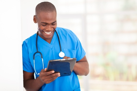 young handsome african american medical worker using tablet computer in hospital photo