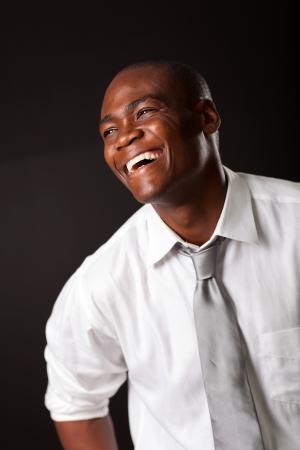 lazo negro: riendo hombre afroamericano sobre el fondo negro Foto de archivo