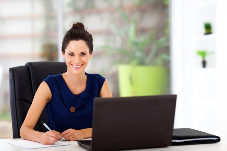 beautiful young office worker sitting by office desk photo