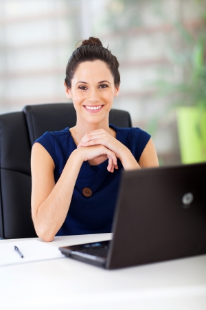 lovely young white collar worker sitting in office photo