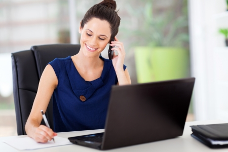 cute young office worker talking on cell phone in office photo