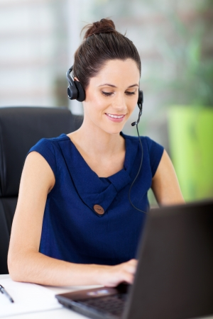 telephonist: beautiful young online support operator working on laptop