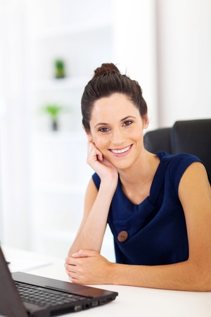 cheerful pretty woman sitting in front of laptop photo
