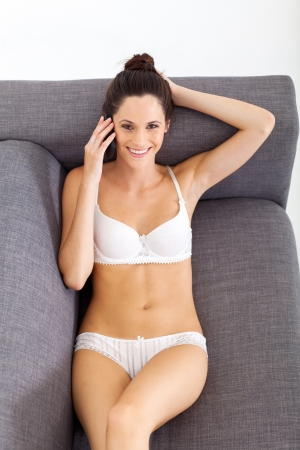 happy young woman in underwear talking on mobile phone photo