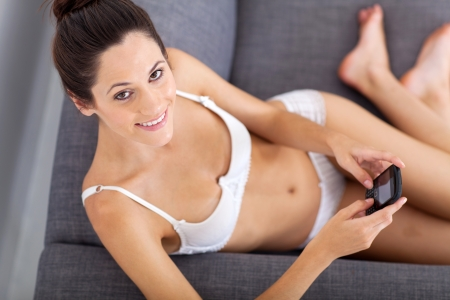 sexy young woman sitting on sofa and emailing from phone photo