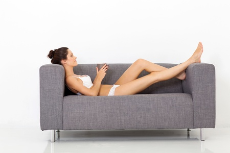 sexy young woman in underwear relaxing on sofa with coffee photo