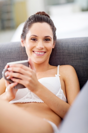 attractive young woman in underwear relaxing at home with coffee photo