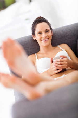 attractive young woman in underwear relaxing on sofa photo