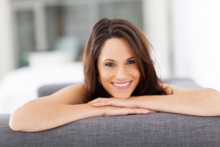 cheerful young woman lying on sofa laughing  photo
