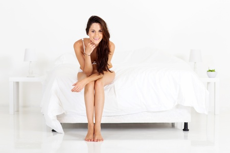cute young woman sitting on bed photo