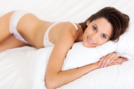 beautiful young woman in underwear lying on bed photo
