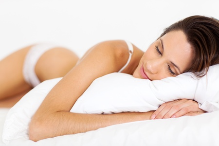 peaceful young woman sleeping on bed photo