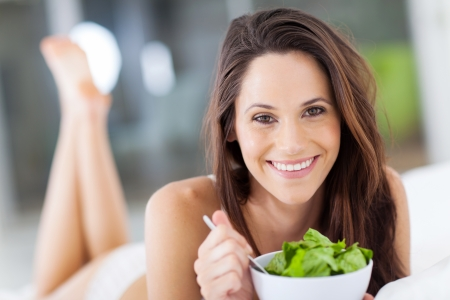happy young woman eating green salad on bed photo