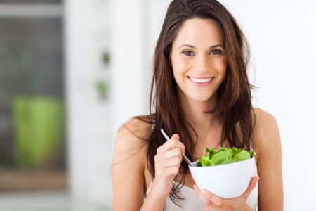 attractive young woman eating healthy salad  photo