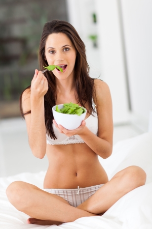 healthy young woman eating green salad on bed photo