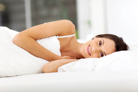 beautiful young woman smiling and sleeping on bed photo