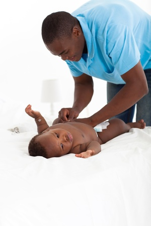 changing: african american father changing baby boys nappie Stock Photo