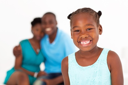 african family: happy african american little girl standing in front of parents