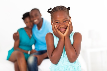 african american mother and daughter: cute african little girl standing in front of parents Stock Photo