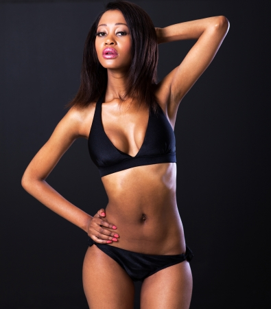 young pretty african american woman in bikini on black background photo